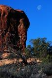 Luna sopra la roccia del deserto ad alba Immagine Stock