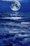 Luna surrealista que asoma sobre el agua tempestuosa azul Foto de archivo