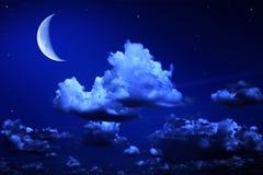 Luna y estrellas grandes en un cielo azul de la noche nublada Imagen de archivo libre de regalías