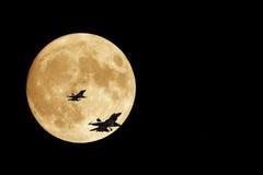 Luna y jets anaranjados F-16 fotografía de archivo