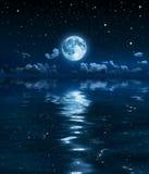 Luna y nubes estupendas en la noche en el mar Foto de archivo