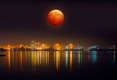 Lunar eclipse. And next to harbor Stock Photo