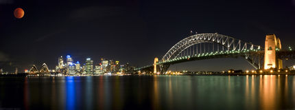 Lunar Eclipse Sydney Harbour. Panoramic view of Lunar eclipse, orange red moon sci-fi scientific scene star war alike over Sydney Harbour Sky Line Panorama At Royalty Free Stock Photo