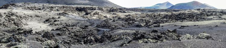 Lunar landscape. Lava field with volcanoes and caldera. In the background. Lanzarote, Canary Islands. Panorama stock photo