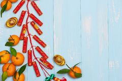 Lunar new year.Firecrackers and Chinese gold ingots and Traditional Red envelopes and decoration with Fresh oranges on wooden royalty free stock photos