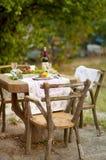 Lunch är romantisk i höstträdgård, atmosfär av ferie och hemtrevlighet Höstlig matställe i den öppna luften med vin och frukt dek royaltyfria bilder