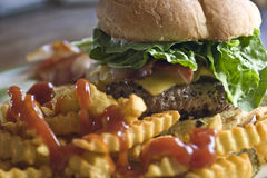 Lunch. A bacon Cheeseburger with Golden crinkle fries and ketchup will make anyone's mouth water Stock Images