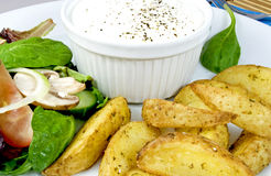 Lunch. Crunchy potato wedges, seasoned with herbs and freshly grounded salt and pepper; decorated with a salad and a bowl with sour cream at the side Stock Photo