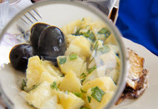 Lunch. Fish,potatoes and olives behind lense Royalty Free Stock Images
