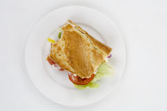 Lunch. A half eaten sandwich on a white plate Royalty Free Stock Images