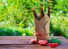 Lunch in aard, gebraden vissen in een document kop, met tomaat en venkel Stock Fotografie