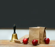 Lunch bags with apples and school bell on desk Royalty Free Stock Photos