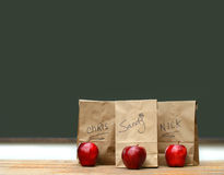 Lunch bags on desk with red apples Royalty Free Stock Images