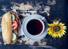 Lunch with a baguette, meatballs, tomato and cucumber and a cup of tea on a wooden background, top view ,toned. Lunch with a baguette, meatballs, tomato and royalty free stock photo