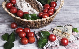 Lunch basket of cherry tomatoes on a branch, bread Stock Photo