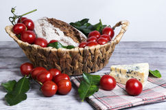 Lunch basket of cherry tomatoes on a branch, bread Royalty Free Stock Photos