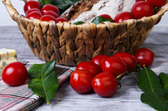 Lunch basket of cherry tomatoes on a branch, bread Royalty Free Stock Images