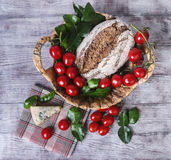 Lunch basket of cherry tomatoes on a branch, bread Stock Images