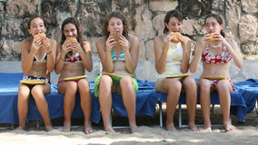 Lunch on the beach. Five teenage girls eating humburgers on the beach Royalty Free Stock Photography
