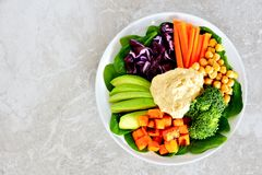 Lunch bowl with fresh vegetables and hummus on marble Royalty Free Stock Images