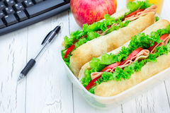 Lunch box with ciabatta bread sandwiches on workplace Royalty Free Stock Image