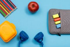 Lunch box, color pencils, apple, headphones and bag-pencil case. With color felt pens and marker on blue background. Top view with copy space. Back to school royalty free stock photos