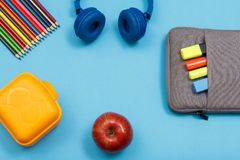 Lunch box, color pencils, headphones, apple and bag-pencil case. With color felt pens and marker on blue background. Top view with copy space. Back to school stock images