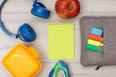 Lunch box, headphones, stapler, yellow notebook, apple and bag-pencil case with color felt pens and marker. On grey wooden background. Top view with copy space royalty free stock image