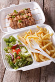 Lunch Box: kebabs, fries and fresh salad in tray close-up. verti Stock Photos