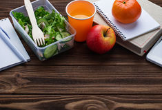 Lunch box with salad, apple, tangerine and juice. Royalty Free Stock Images