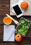 Lunch box with salad, notebook and phone Royalty Free Stock Images