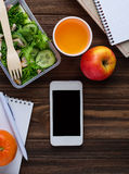 Lunch box with salad, notebook and phone Royalty Free Stock Image