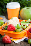 Lunch box with sandwich and fruits. Lunch box for kids with sandwich, cookies, fresh veggies and fruits stock photo