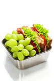 Lunch box with sandwich and grapes Stock Images