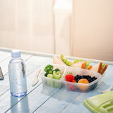 Lunch box with sandwich, vegetables, fruits and bottle of water. Healthy lunch box with sandwich, fresh vegetables, fruits and bottle of water on blue wooden Royalty Free Stock Photo