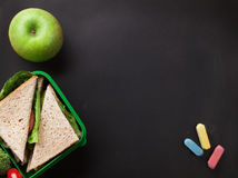 Lunch box. With sandwich and vegetables. Kids take away food box. Top view on blackboard with space for your text stock photos