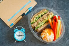 Lunch box with sandwich, vegetables, water and fruits on black chalkboard. Lunch box with sandwich, vegetables, water and ts on black chalkboard. Healthy eating Stock Photos