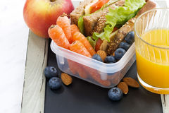 Lunch box with sandwich of wholemeal bread on blackboard. Closeup Stock Photo