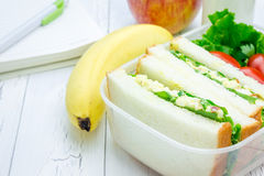 Lunch box with sandwiches, fruits, milk and stationery Stock Photography