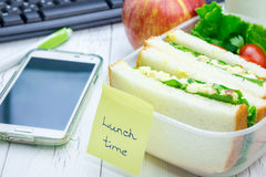 Lunch box with sandwiches, fruits, and milk on workplace Royalty Free Stock Image