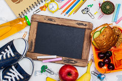 Lunch box and school supplies. Chalkboard for your text. Flat lay style Royalty Free Stock Images
