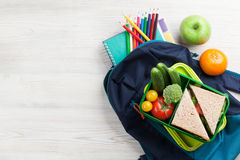 Lunch box and school supplies. Lunch box with vegetables and sandwich on wooden table. Kids take away food box and school backpack. Top view with copy space royalty free stock photography