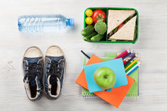 Lunch box and school supplies. Lunch box with vegetables and sandwich on wooden table. Kids take away food box and school supplies. Top view stock photo