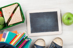Lunch box and school supplies. Lunch box with vegetables and sandwich on wooden table. Kids take away food box and school supplies. Top view with blackboard for royalty free stock photography
