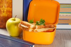 Lunch box with toasted slices of bread, cheese and green parsley, green apple and hardback books on the background. Yellow lunch box with toasted slices of bread stock image