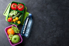 Lunch box. With vegetables, fruits and water bottle. Kids take away food box. Top view on blackboard with space for your text royalty free stock photography