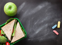 Lunch box. With vegetables and sandwich. Kids take away food box and apple. Top view on blackboard with space for your text stock photo