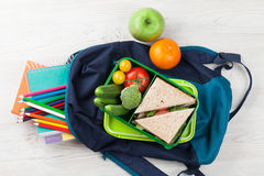 Lunch box. With vegetables and sandwich on wooden table. Kids take away food box and school backpack. Top view royalty free stock images
