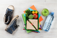 Lunch box. With vegetables and sandwich on wooden table. Kids take away food box and sneakers. Top view Royalty Free Stock Photography