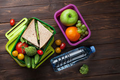 Lunch box. With vegetables and sandwich on wooden table. Kids take away food box. Top view Stock Photos